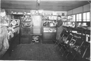 Ralph H Swope behind counter in old store (1934)