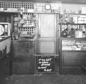 Ralph H Swope behind counter in old store (1935)